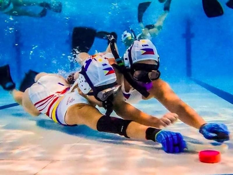 People playing underwater hockey