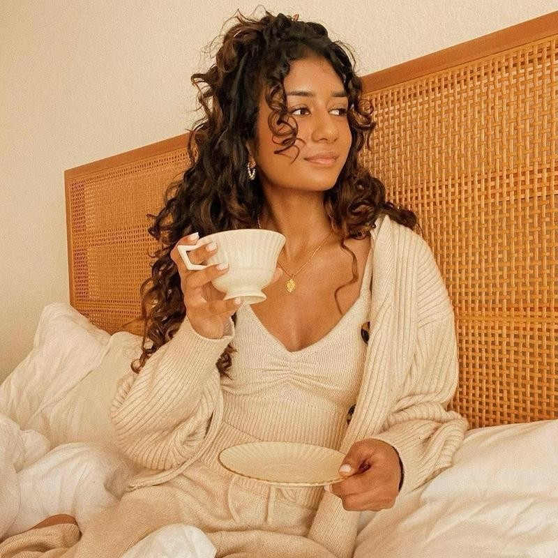 Woman in bed in knit outfit with tea