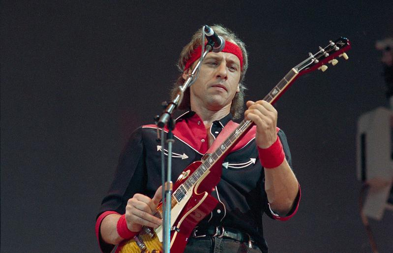 """""""Money for Nothing"""" writer Mark Knopfler of Dire Straits plays his guitar at the Live Aid concert in London, England, in 1985, the year the song hit No. 1 on the Billboard Hot 100 chart."""