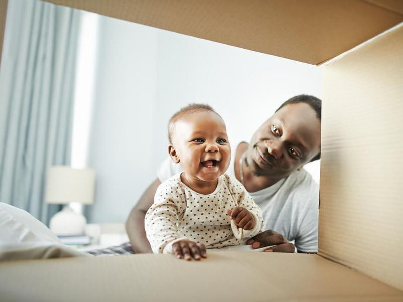 Baby girl and her father playing with a cardboard box at home