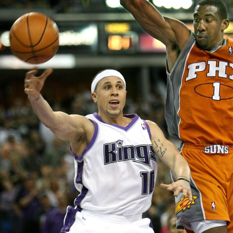 Mike Bibby passes around Amare Stoudemire of the Phoenix Suns
