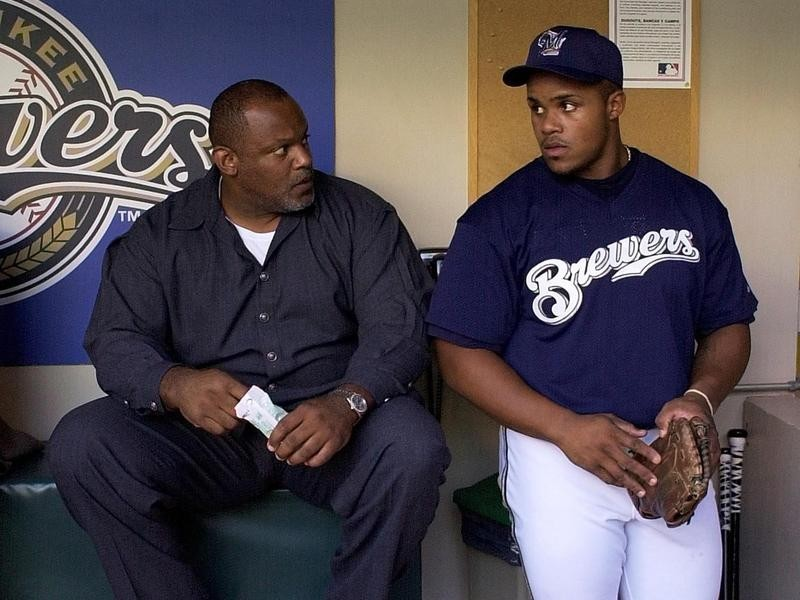 Prince Fielder talks to father Cecil Fielder in dugout in Milwaukee