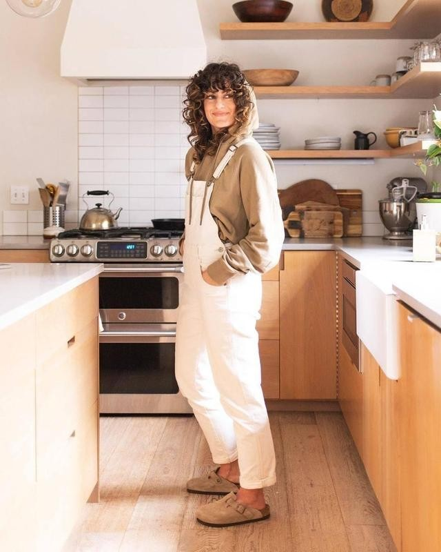 Woman in overalls in kitchen