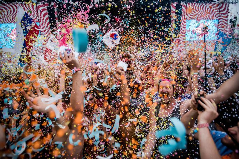 Festival goers throw confetti at each other at 24th Sziget Festival