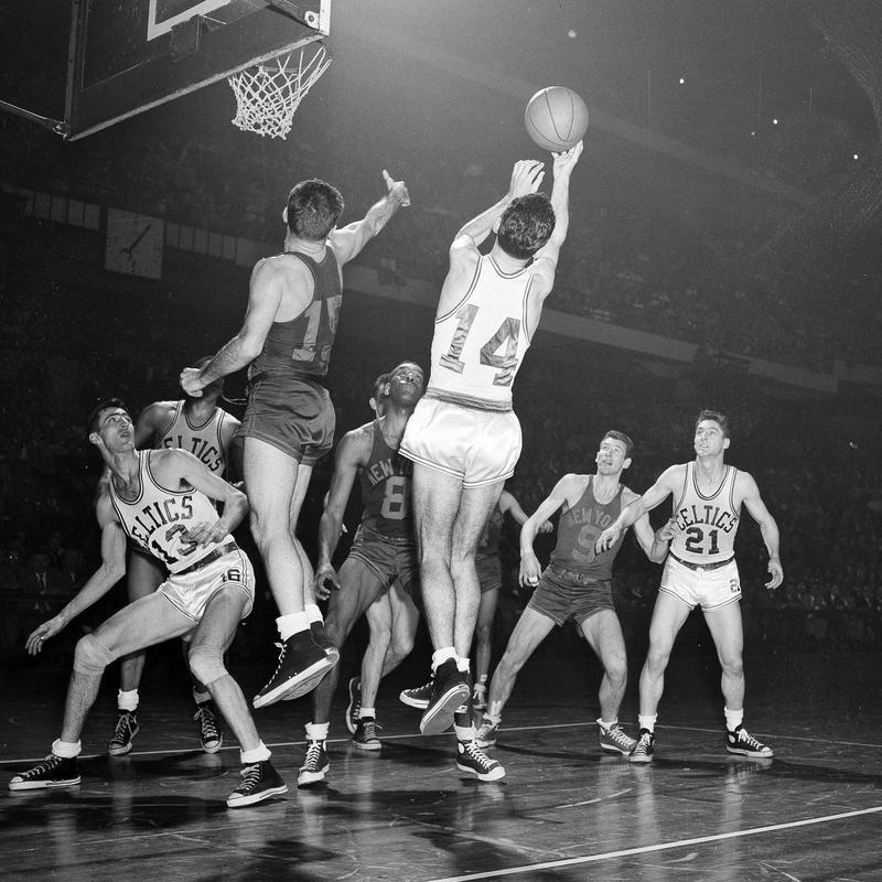 Boston Celtics Bob Cousy takes a rebound off