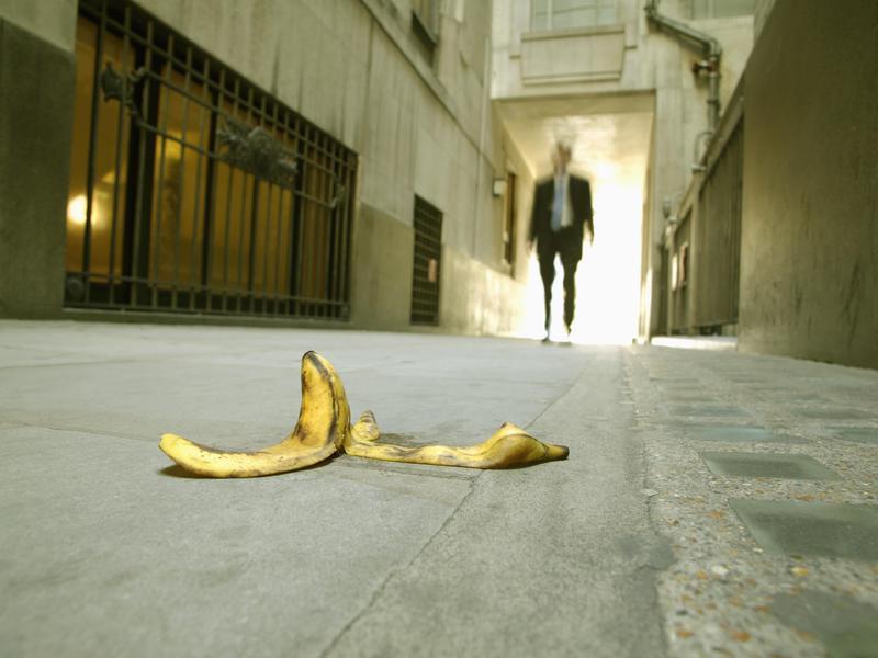 Businessman walking toward a banana peel