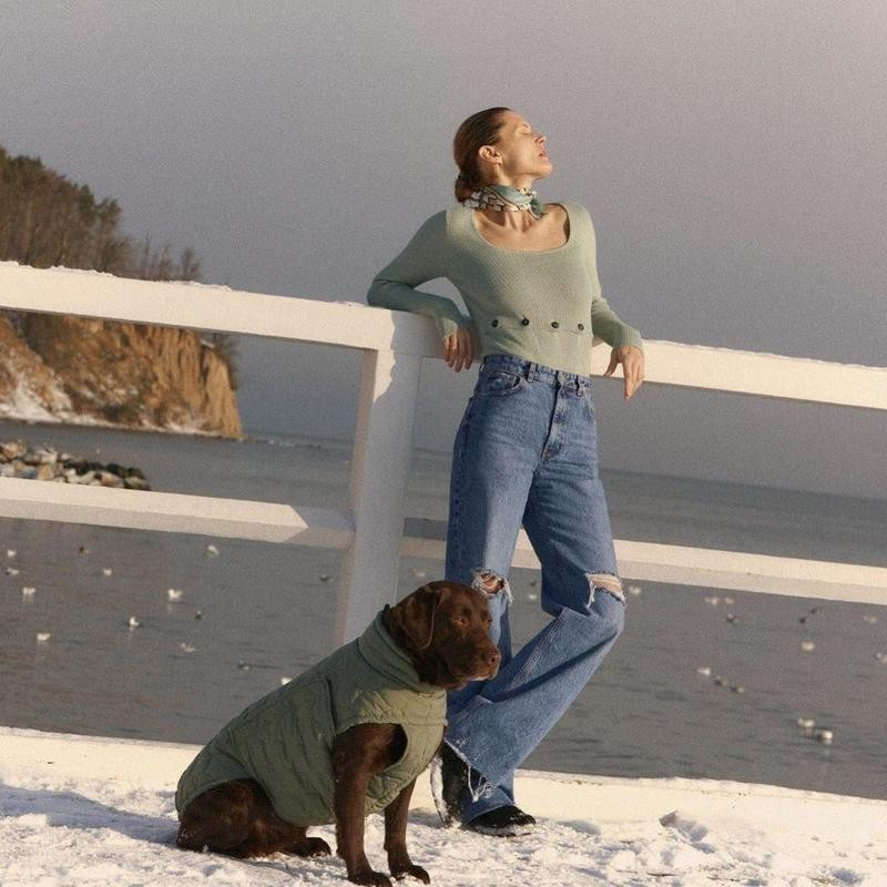 Woman and dog in olive green attire by water