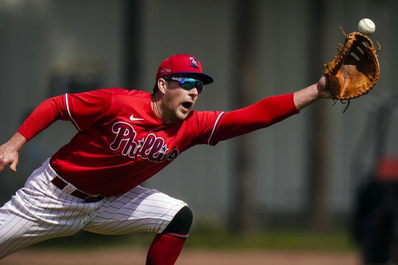 Rhys Hoskins of the Philadelphia Phillies reaches for ball