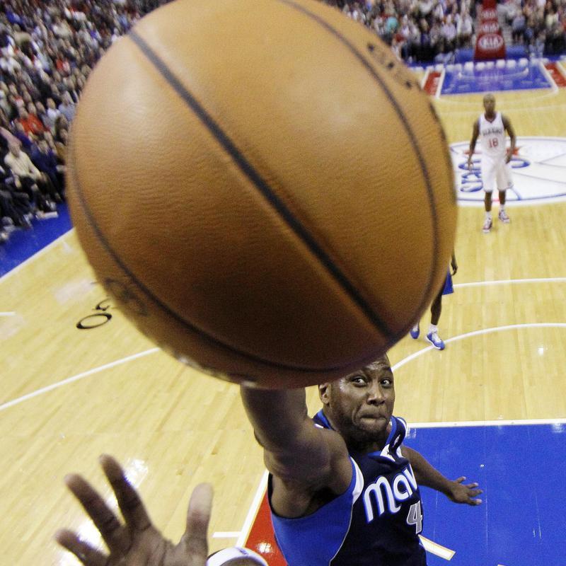 Philadelphia 76ers' Kwame Brown goes up for shot as Dallas Mavericks' Elton Brand defends