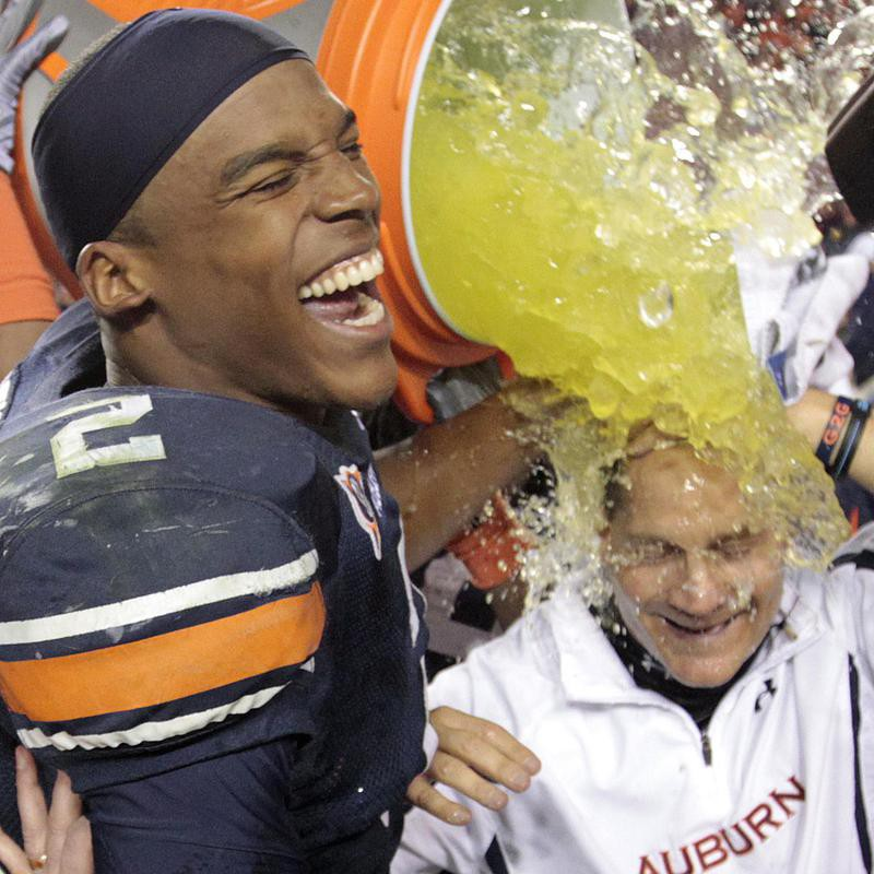 Auburn quarterback Cameron Newton dunks coach Gene Chizik