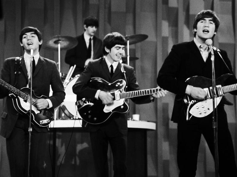 """The Beatles perform on """"The Ed Sullivan Show"""" in New York in 1964, the year Beatlemania broke and """"Can't Buy Me Love"""" rose to No. 1 on the Billboard Hot 100 chart."""