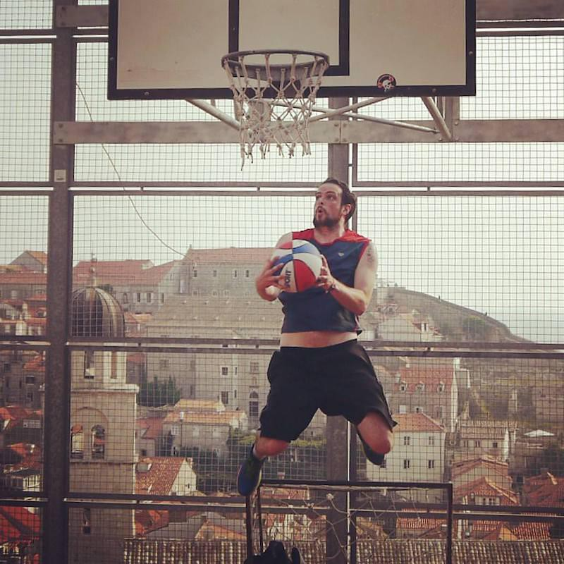 Man playing basketball at City Wall Rooftop Court