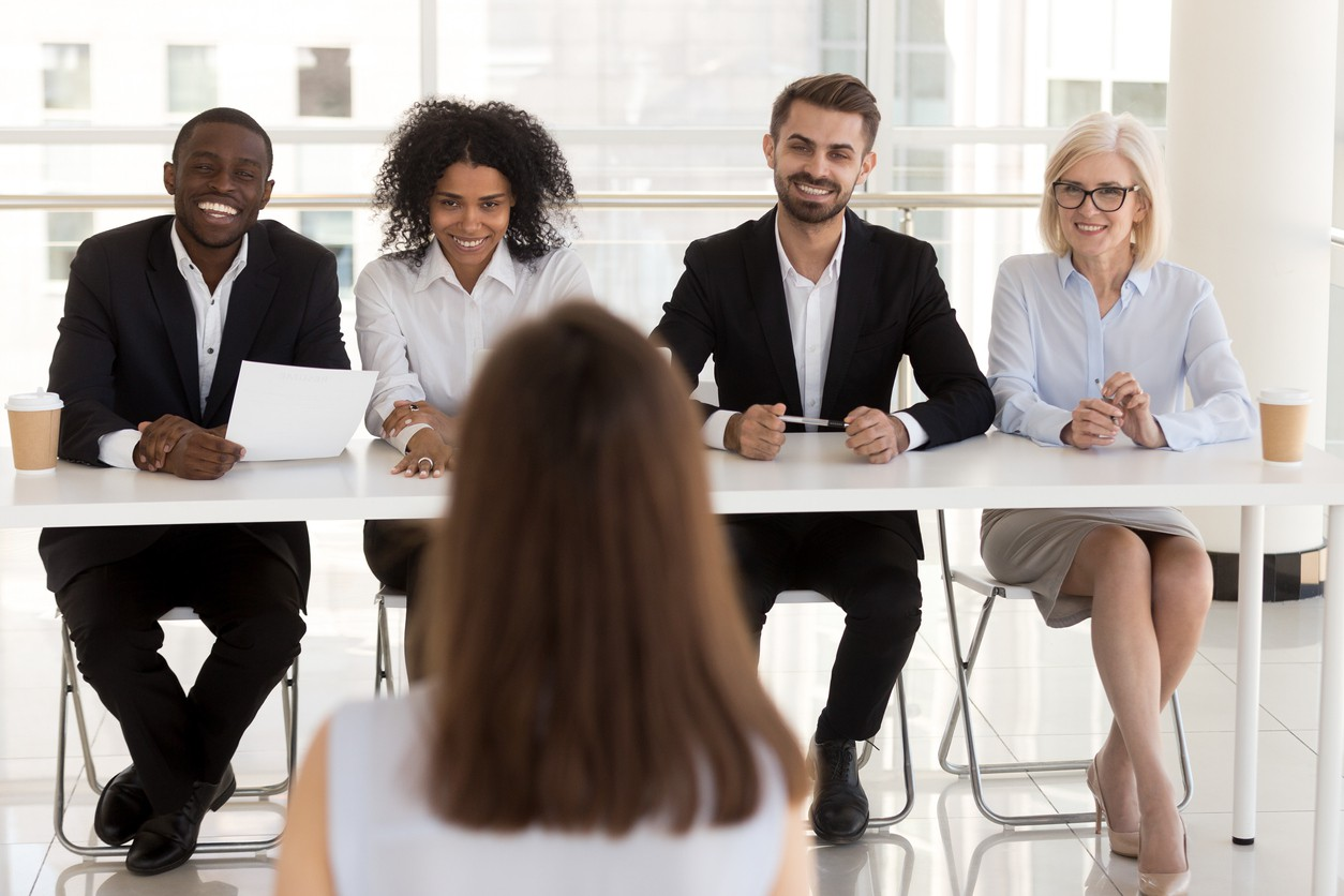 Several people interviewing a woman for a job