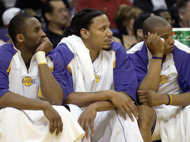 Los Angeles Lakers' Kobe Bryant, Brian Grant, and Caron Bulter watch from bench