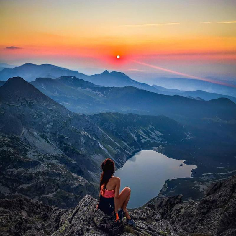 Woman watching the sunrise over Tatra National Park