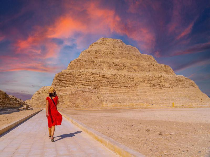 A young tourist in a red dress at the Stepped Pyramid of Djoser