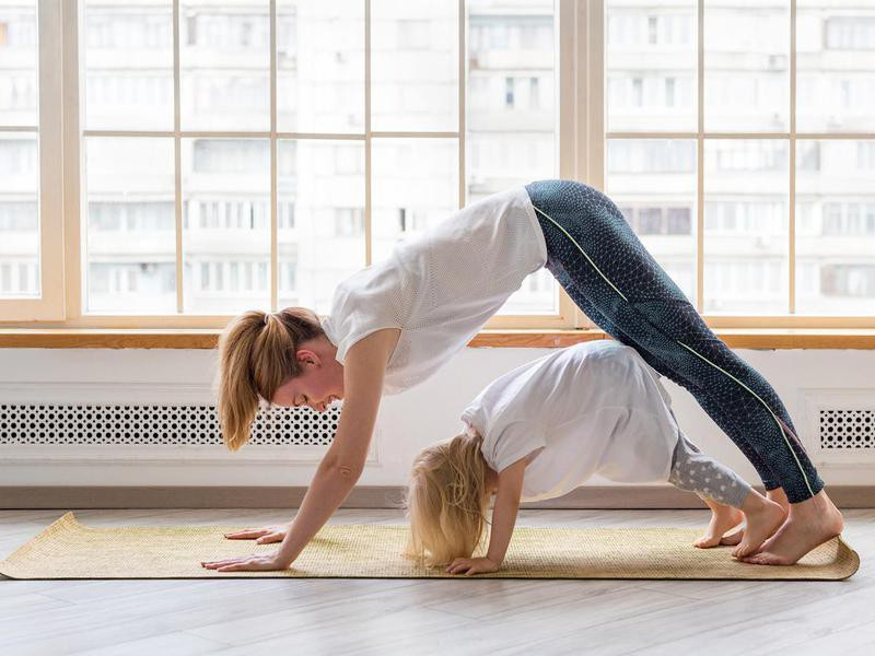 Mother and daughter doing easy yoga poses for kids