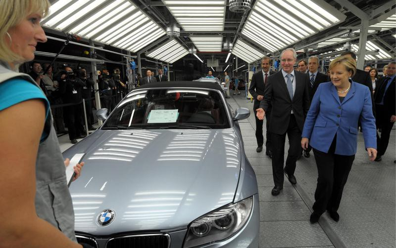Angela Merkel and other people surveying BMW car