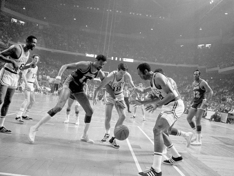 Sam Jones looks to gain control of loose ball with Bailey Howell against Wilt Chamberlain