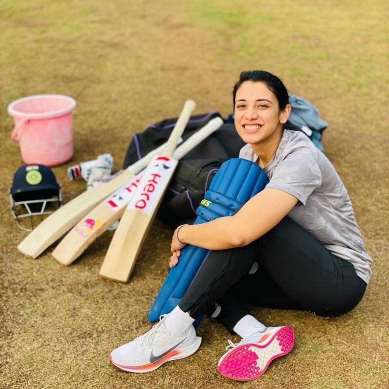 Smriti Mandhana posing with her cricket gear