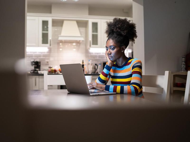 African Woman responding to emails at home at night