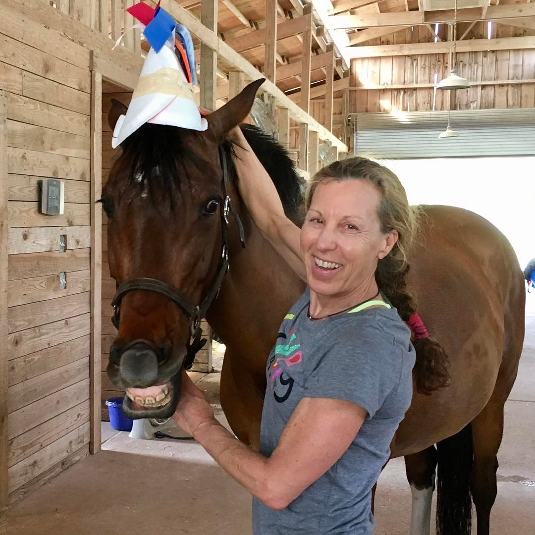 Woman posing with horse smiling for birthday