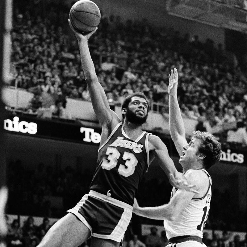 Kareem Abdul-Jabbar hooks one over Dave Cowens