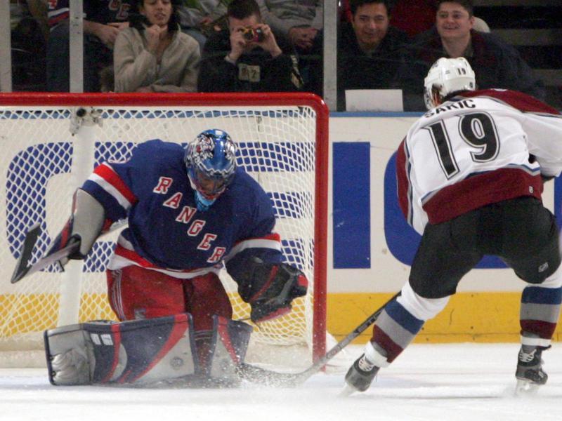 Joe Sakic scores a penalty goal against New York Rangers goalie Kevin Weekes
