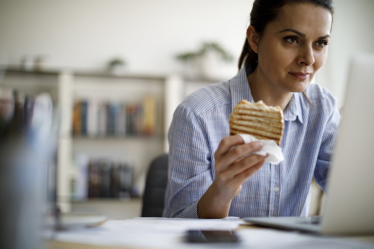 Woman eating and working