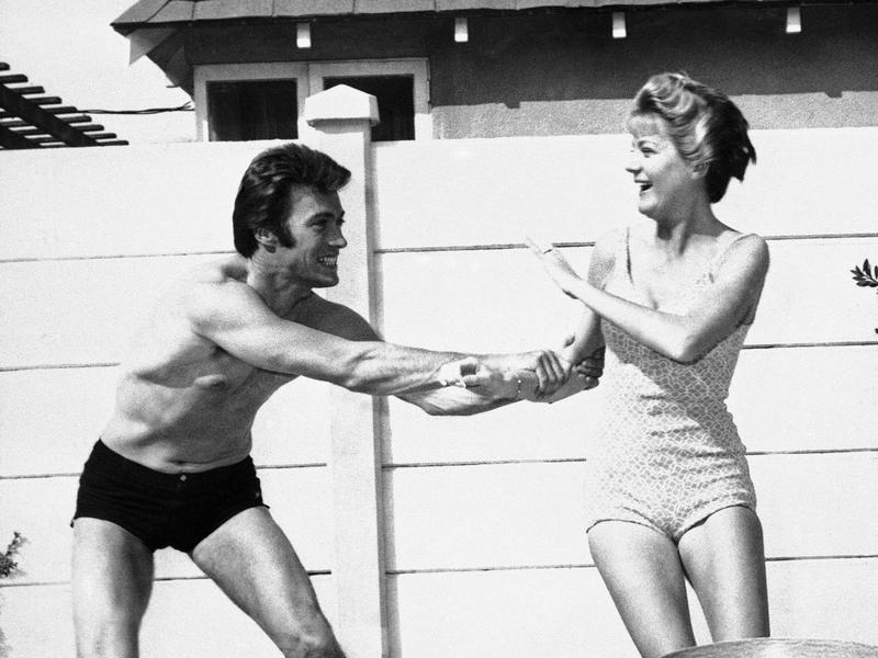 Clint Eastwood frolics with his then-wife Maggie in the swimming pool outside their Hollywood home in 1960.