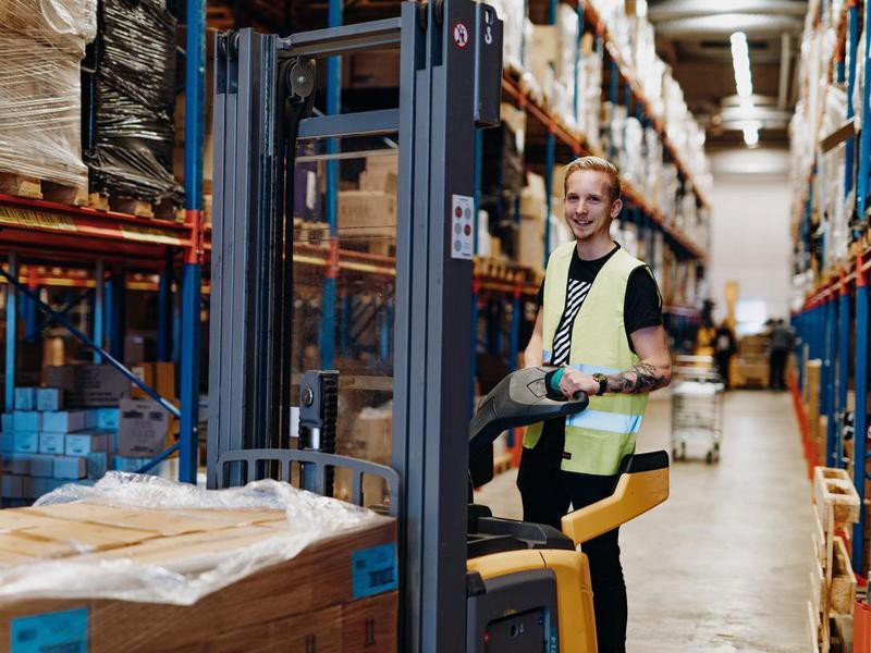 Employee in warehouse, driving forklift
