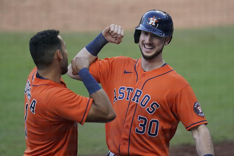 Kyle Tucker of the Houston Astros celebrates his solo home run with Carlos Correa