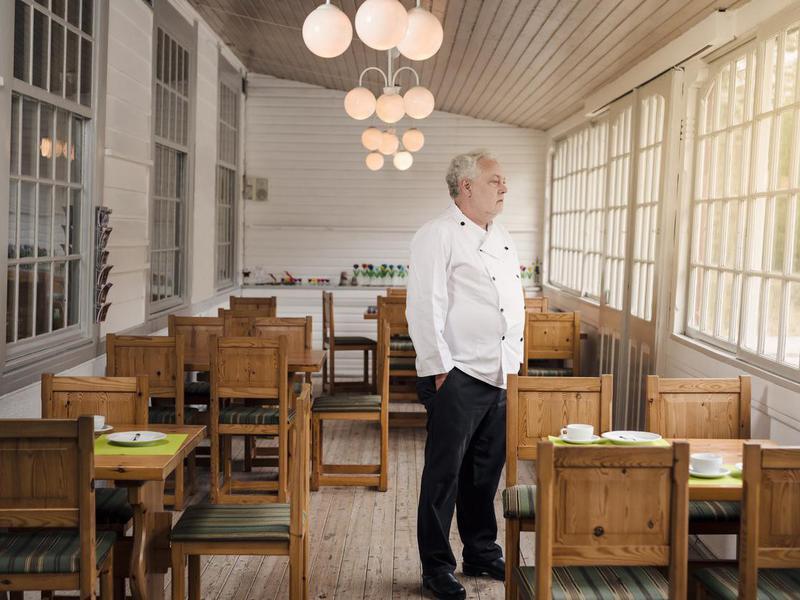 Restaurant owner standing in an empty restaurant.