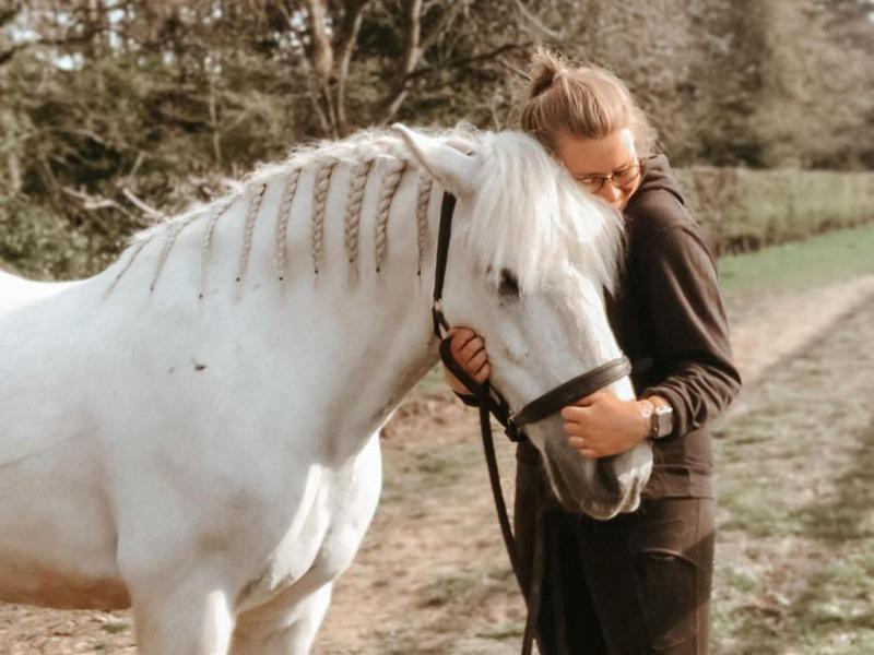 Young woman cuddling her Highland Pony