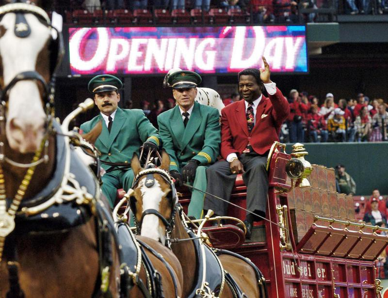 Lou Brock waves to crowd riding on Budweiser Clydesdales