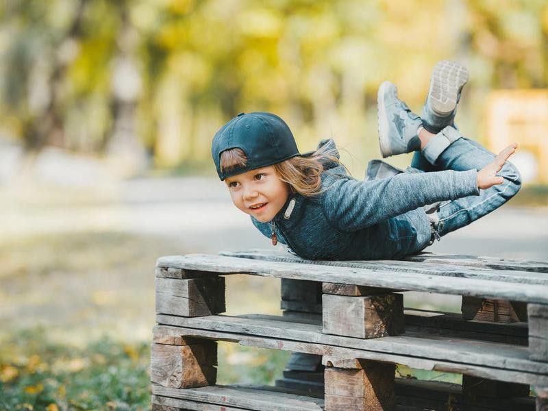 Little boy trying easy locust yoga pose