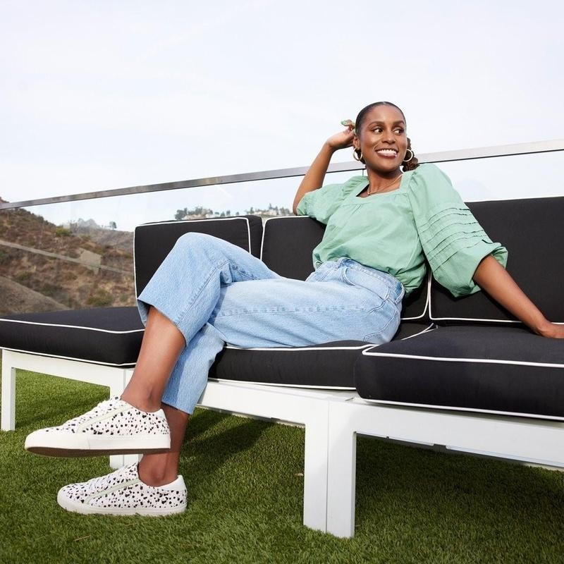 Issa Rae sitting on couch in Madewell clothing