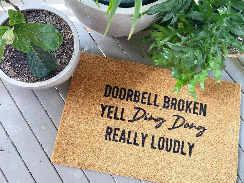 Funny doormat surrounded by houseplants