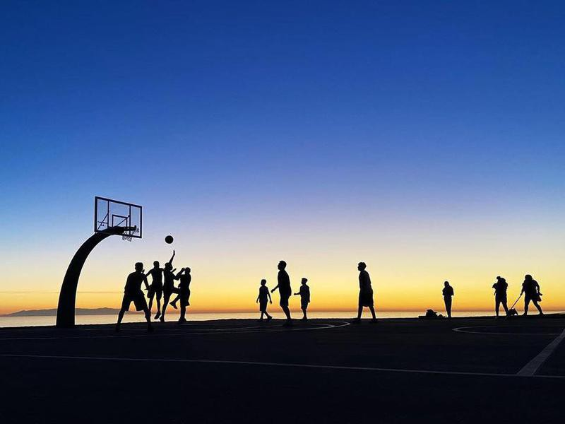 People playing Angels Gate Park Basketball Court at sunset