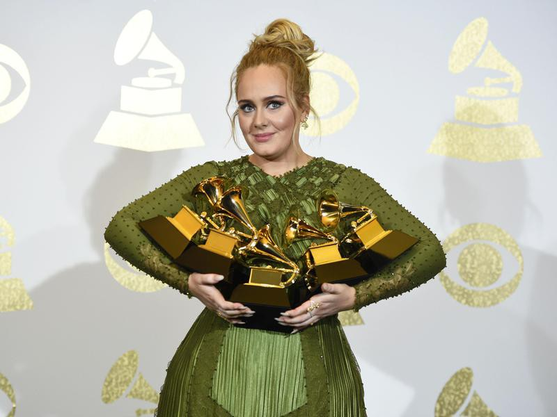 Adele posing with her Grammys