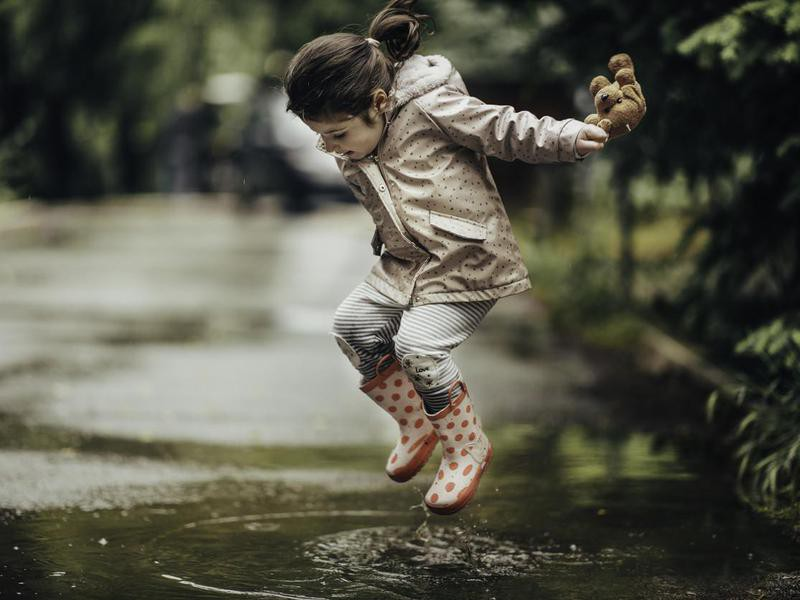 Smiling little girl playing in a puddle