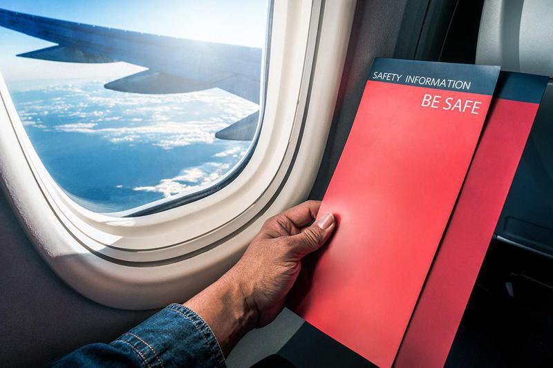 Man reading flight safety instructions