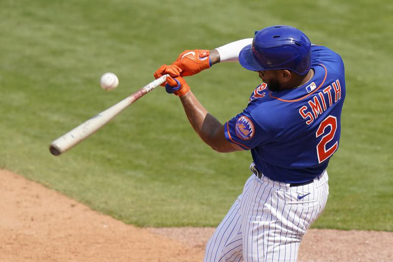 Dom Smith bats during spring training game