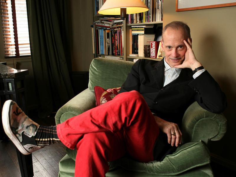 John Waters sitting at home