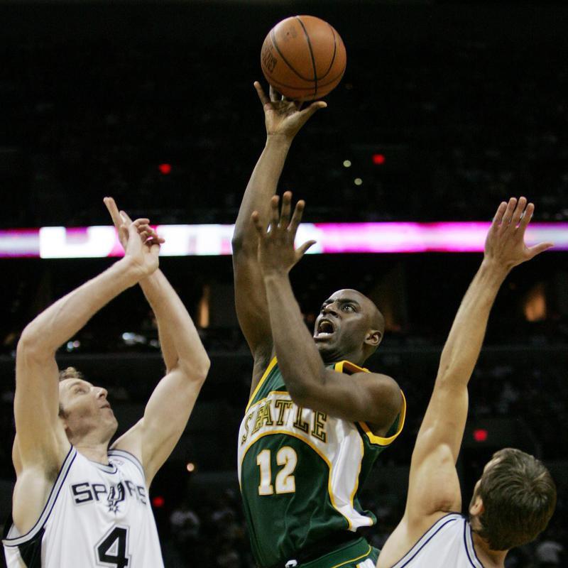 Seattle SuperSonics forward Damien Wilkins drives between San Antonio Spurs defenders