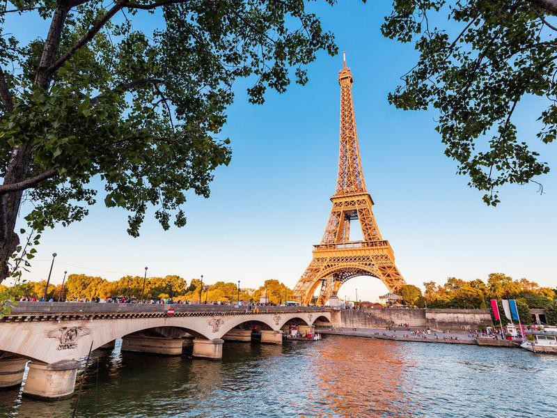 Panoramic view of Eiffel tower and Seine river at sunset.