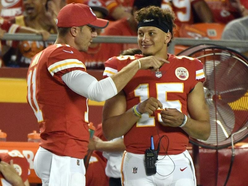 Alex Smith talks to Patrick Mahomes during a 2017 game
